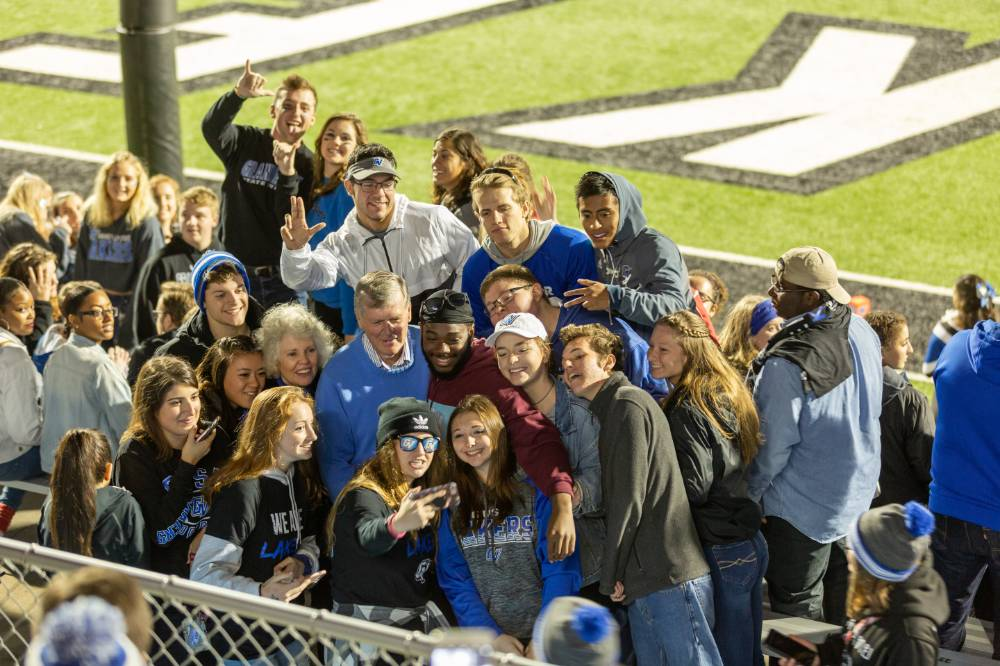 students taking selfies with T. Haas and his wife at a GVSU football game